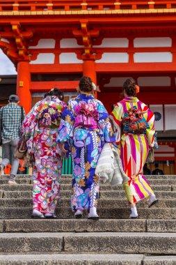 Young women wearing traditional japanese kimonos at Fushimi Inari Shrine in Kyoto