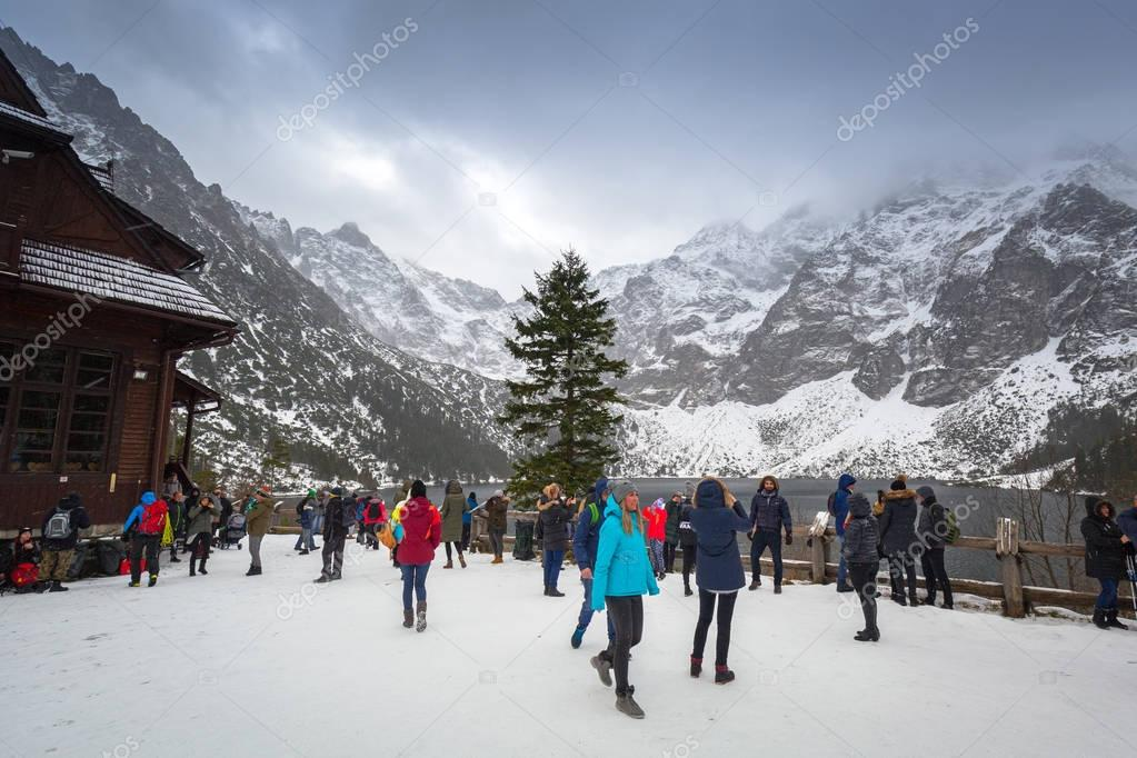 ZAKOPANE, POLAND - NOVEMBER 11, 2017: Tourist at Morskie Oko lake (Eye of the Sea) in Tatra mountains, Poland. Morskie Oko located in the Tatra National Park is popular tourist destination in Poland.