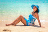 Szép nő, a trópusi tengerparton kék kalapban