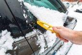 Škrábání zmrzlého sněhu z oken automobilu