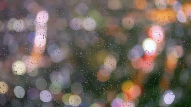 Dešťové kapky na okno s pouliční bokeh světla