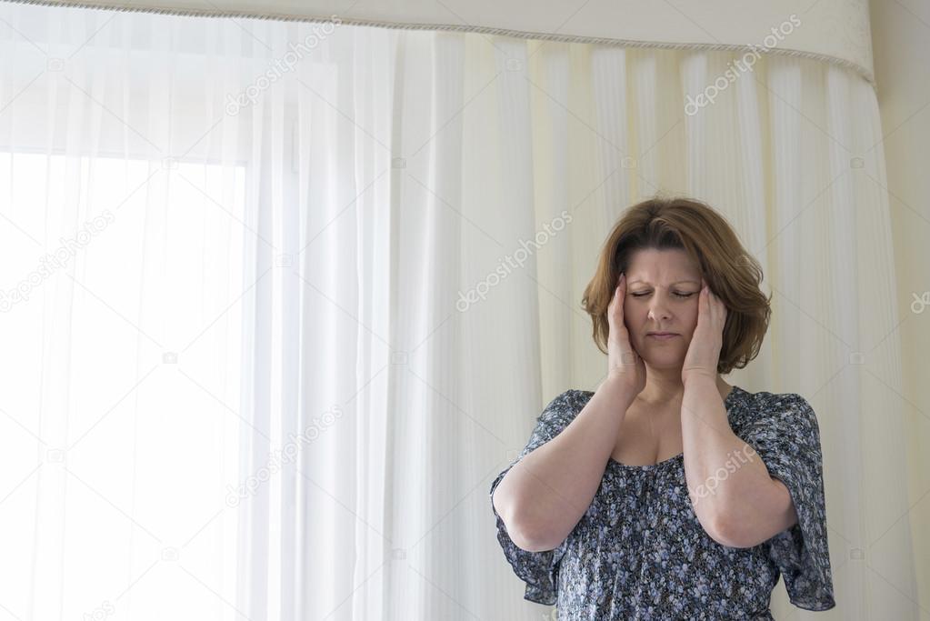 vrouw moe hang gordijnen te ervaren hoofdpijn — Stockfoto © olenka ...