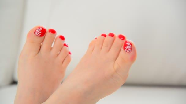 Ženské nohy s květinovým vzorem a Červený lak na nehty