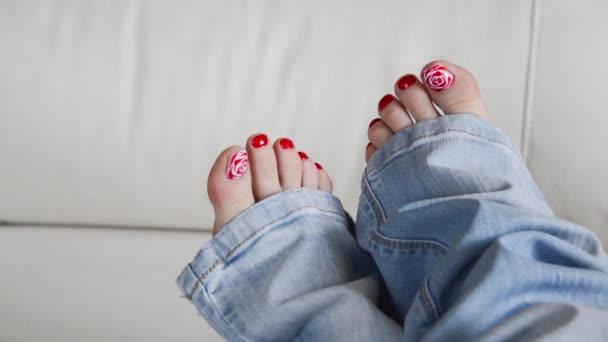 Ženské nohy s Červený lak na nehty na gauči