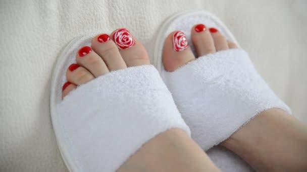 Ženské nohy v bílé pantofle na gauči