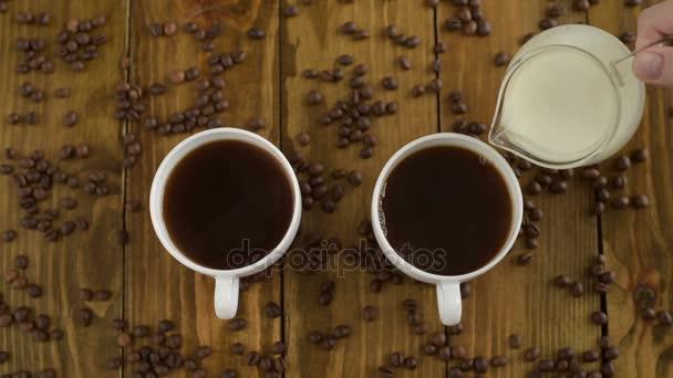 Nalévá mléko do šálků kávy