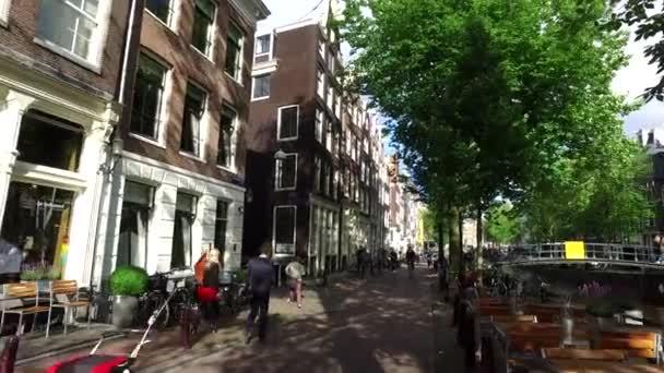 05 červenec 2016: Amsterdam, Nizozemsko: pohled z ulice a město Amsterdam známého canal Holland s turistických lodí. Nizozemsko Amsterdam Evropa kanál ulice Holandsko Nizozemsko záběry 4k