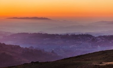 Sunset sky above layers of foggy mountains