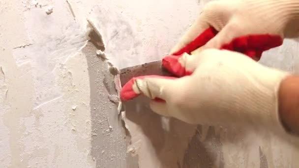 Video z rukou v rukavicích, odstranění starých tapet s spatuladuring domácí opravy