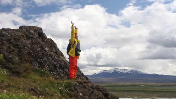 Young woman in bright clothes enjiying nature of Iceland