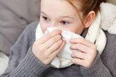 Porträt eines Mädchens, das im Bett die Nase pustet, Krankheitskonzept