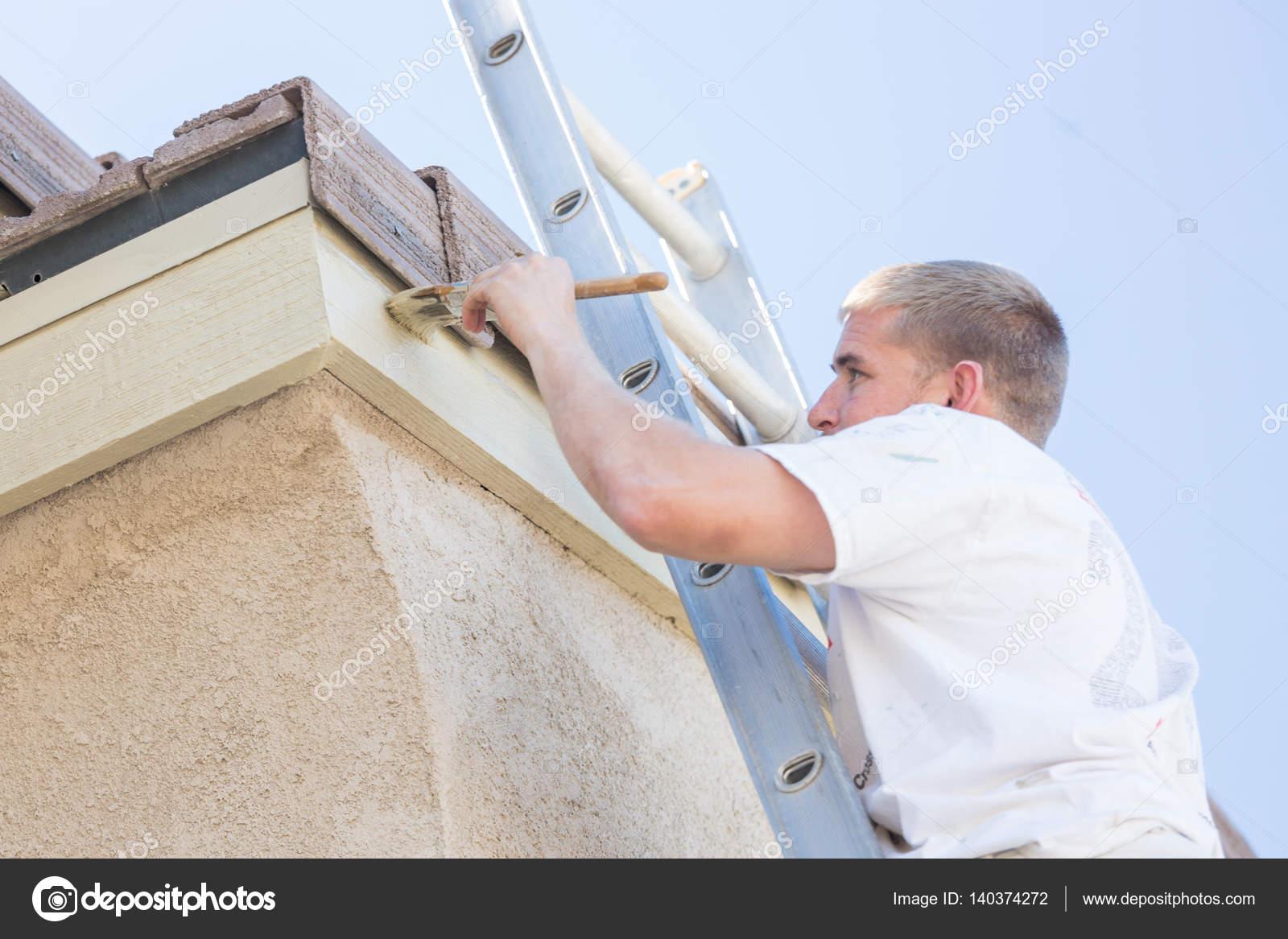 Pintor profesional con rodillo pequeño para pintar casa Fascia ...
