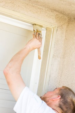Professional Painter Cutting In With Brush to Paint Garage Door Frame