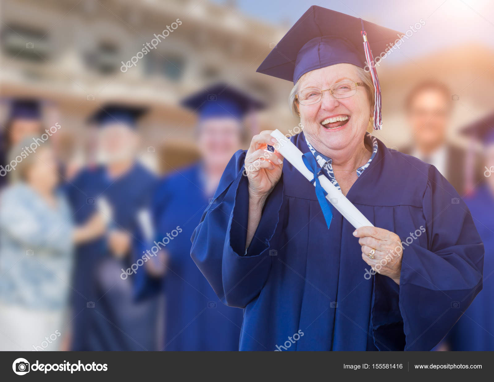Happy Senior Adult Woman In Cap and Gown At Outdoor Graduation C ...