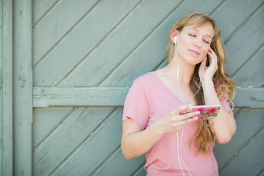 Outdoor Portrait of Young Adult Brown Eyed Woman Listening To Music with Earphones on Her Smart Phone.