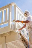 Photo Professional House Painter Wearing Facial Protection Spray Painting Deck of A Home.