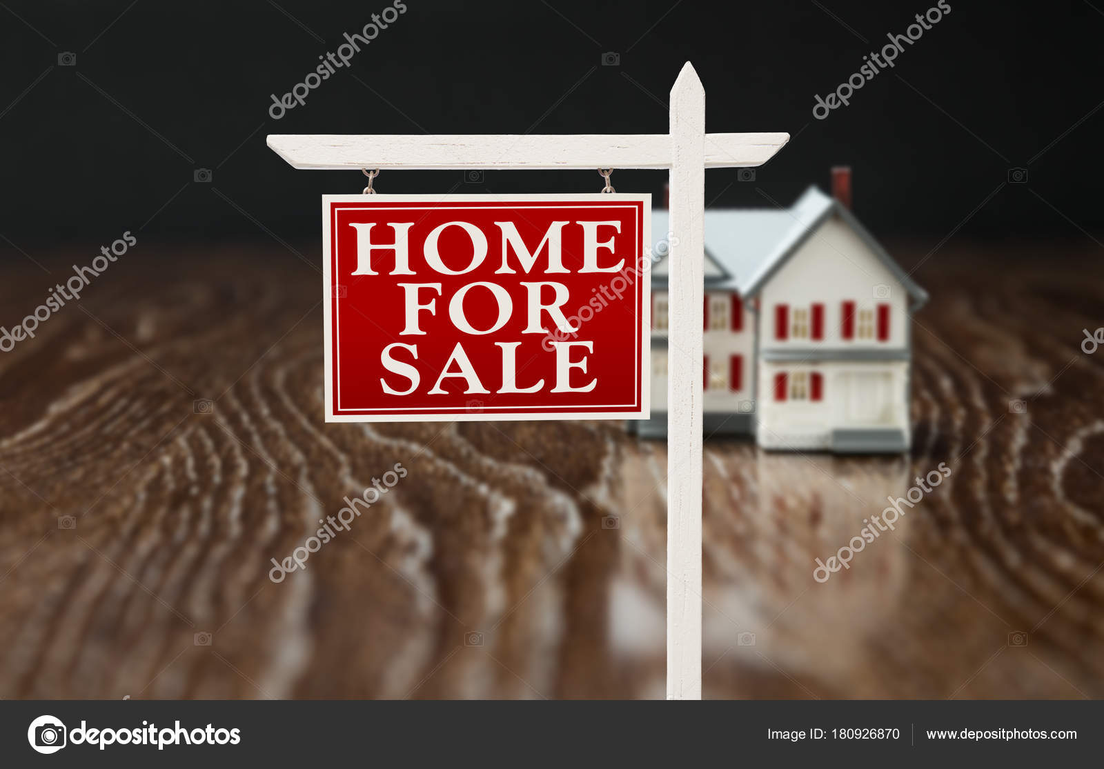 for sale real estate sign in front of model home on reflective