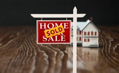 Sold For Sale Real Estate Sign In Front of Model Home on Reflective Wooden Surface.