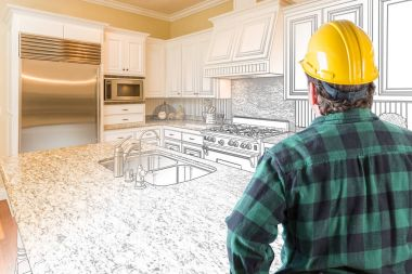 Male Contractor with Hard Hat Looking At Custom Kitchen Drawing Photo Combination On White.