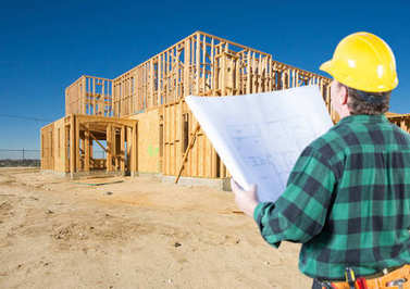 Contractor with Plans and Hard Hat Looking At New House Framing at Construction Site.