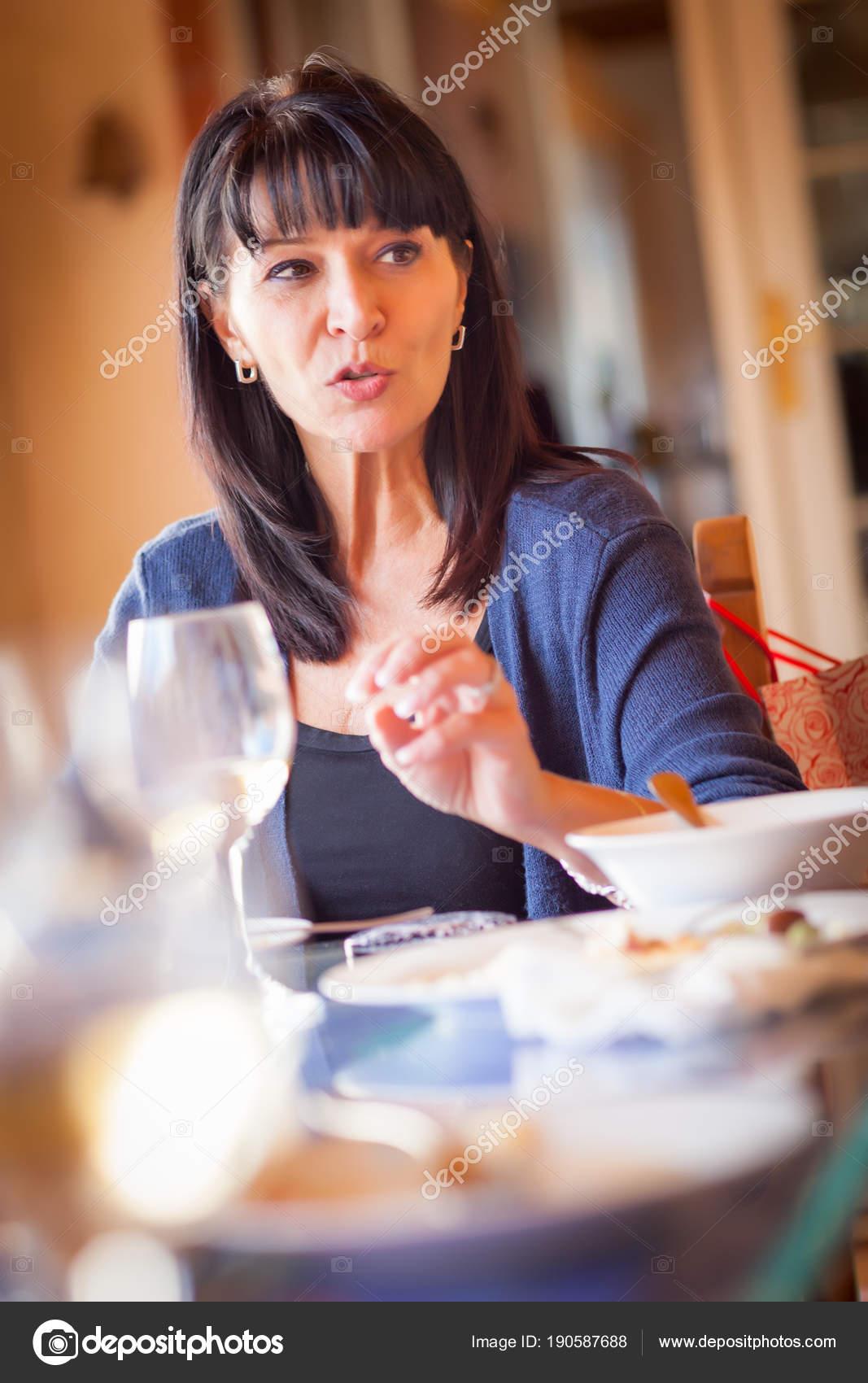 Ziemlich Italienerin genießt eine Mahlzeit und Getränke mit Freunden ...