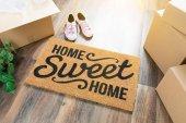 Fotografie Domov, sladký domov rohožku, pohybující se krabice, růžové boty a rostlin na tvrdé dřevěné podlahy