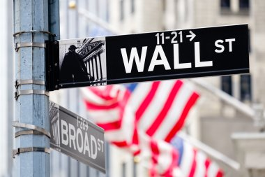 Wall street sign in New York City with american flags on the bac