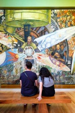 Visitors admiring the murals by Diego Rivera at the Palacio de Bellas Artes in Mexico City