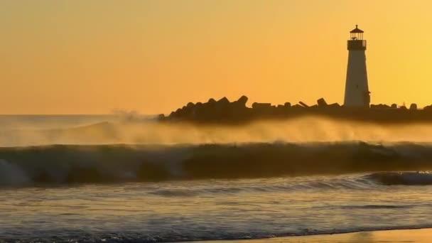 The Santa Cruz Breakwater (aka Walton) Maják při západu slunce, jak je vidět z Twin Lakes Beach v Santa Cruz, Kalifornie, USA, 2018