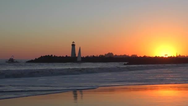 Neidentifikovaní lidé na Twin Lakes Beach v Santa Cruz Harbor při západu slunce, na severní Monterey Bay v Santa Cruz County, Kalifornie, USA.