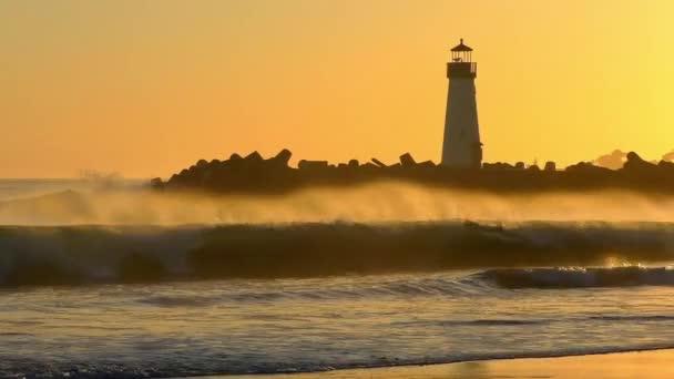 The Santa Cruz Breakwater (aka Walton) Maják při západu slunce, jak je vidět z Twin Lakes Beach v Santa Cruz, Kalifornie, USA.