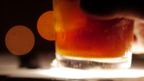 Tmavě zbarvené koktejl s ledem. Detailní záběr na rozmazané pozadí. Ruka ho.