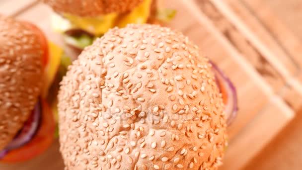 Tři čerstvé chutné hamburgery se salátem a rajčaty. Closeup