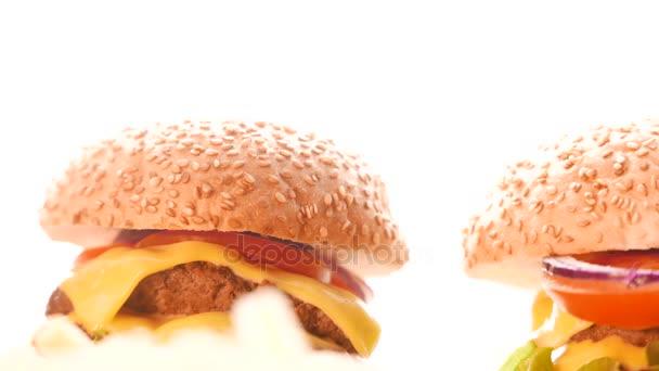 Hamburger s cibulí, rajčaty a salátem na světlé pozadí