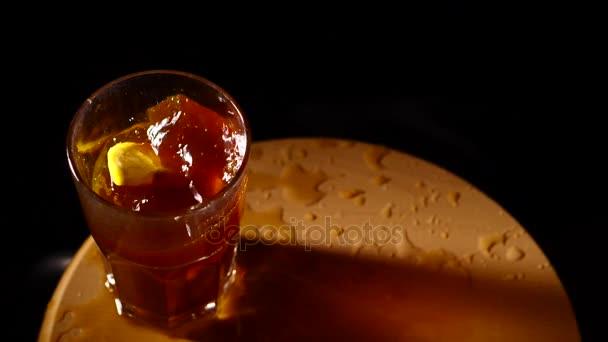 Zitronenscheiben fallen in das Glas mit Cocktail-Zeitlupe