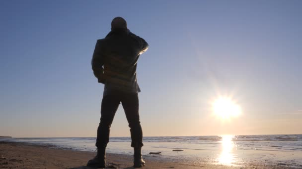 Silhouette of lonely man at sea shore