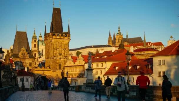 Lidé chodící po Karlově mostě při západu slunce, Praha, Česká republika.