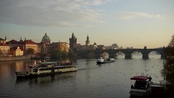 Lodě plovoucí pod Karlovým mostem při západu slunce, Praha.