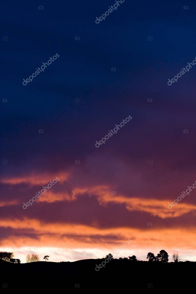 Dramatic Sunset on Curved Landscape with Trees