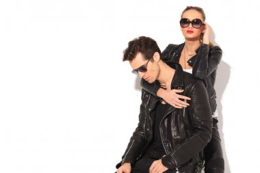 woman in leather jacket embracing seated man from behind