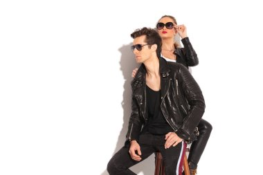 young couple in leather jackets looking away