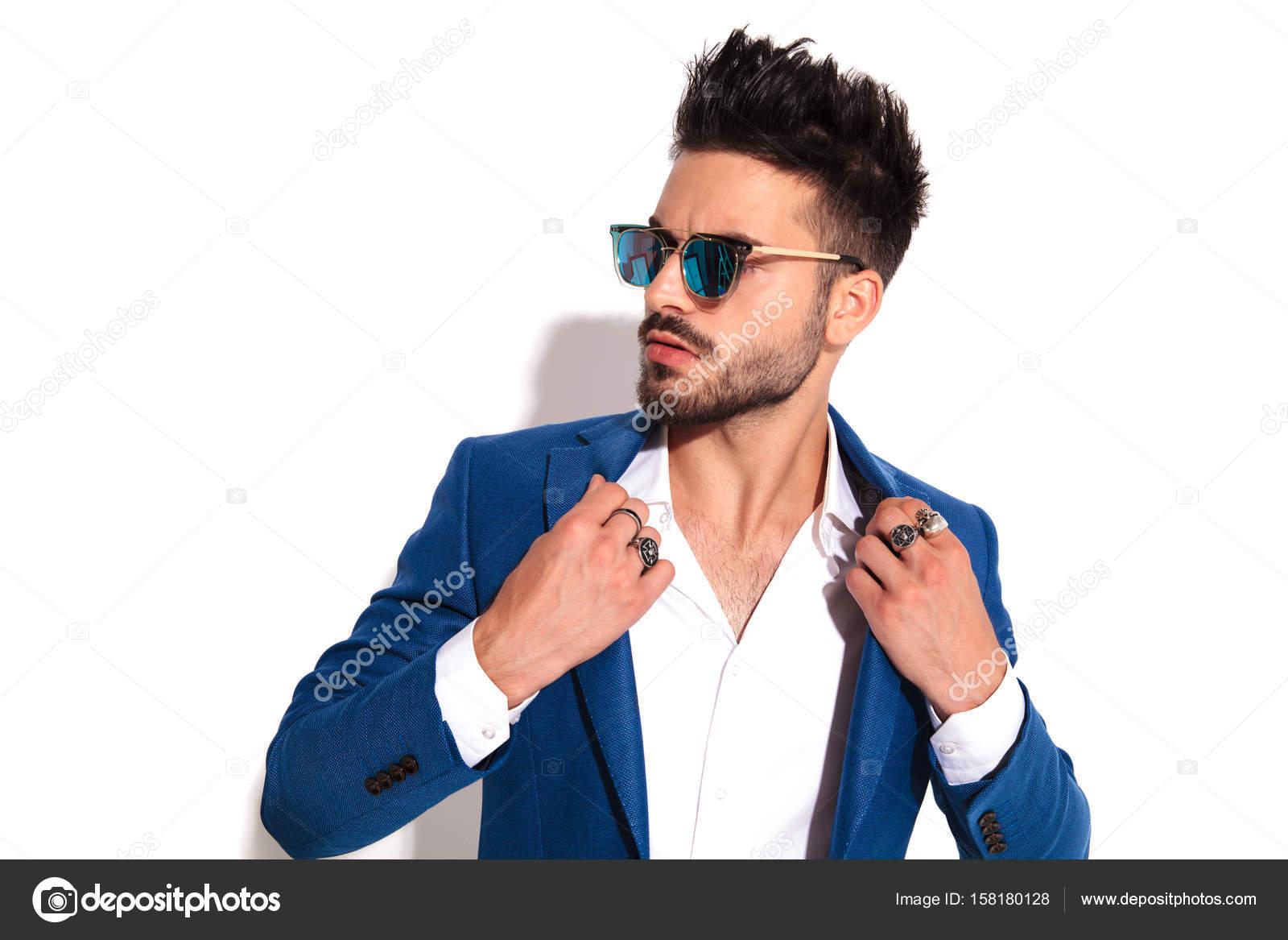 addea384c6167b Nahaufnahme von jungen sexy Mann in Sonnenbrille hält seinen Kragen und  blickt zur Seite auf weißem Hintergrund — Foto von ...