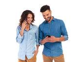 Frau im Gespräch und Mann SMS auf Handy
