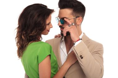 man with hand on sunglasses smiles at his woman