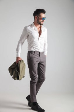 side view of a man walking with hand in pocket