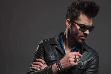 young hipster wearing rings, sunglasses and leather jacket looks