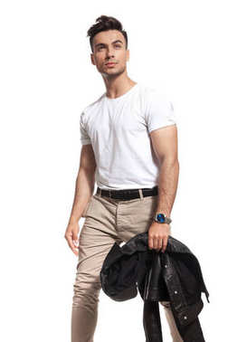 young casual man holding jacket looks up