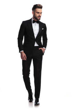 serious handsome man in tuxedo walks and looks to side