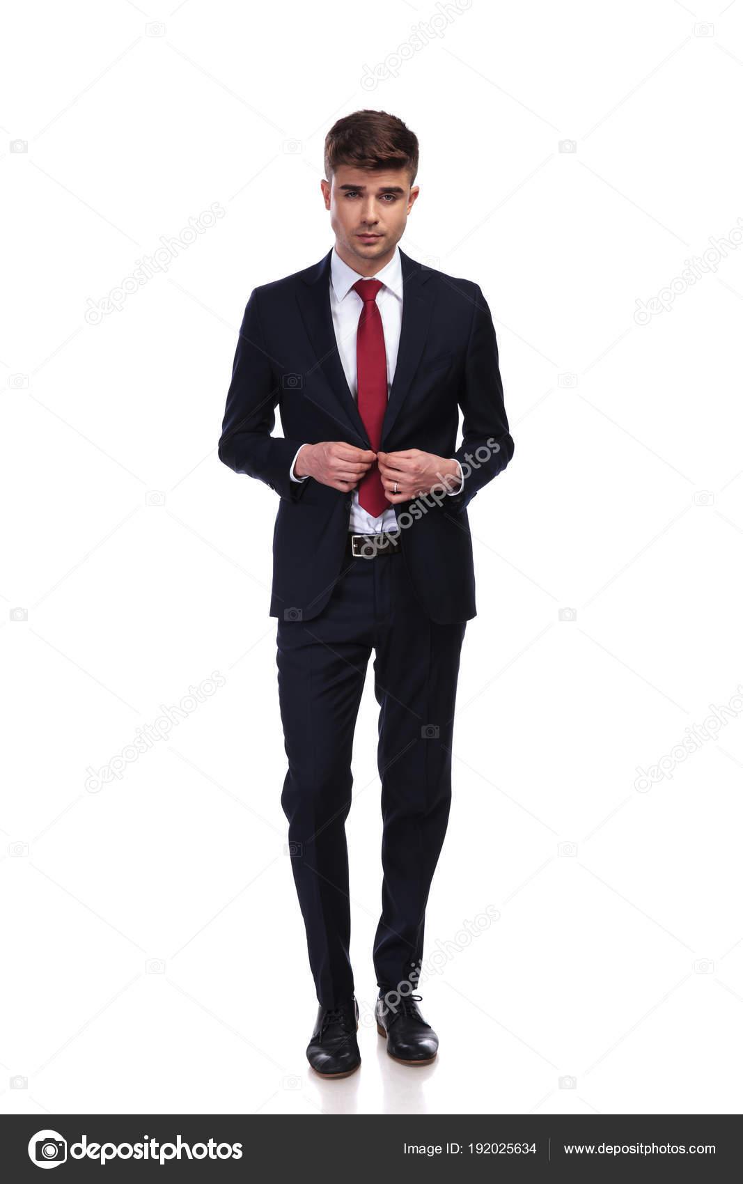 877355fe5b270 Homme d'affaires sexy boutonner son veston en marchant sur fond blanc. Il  porte un costume de couleur marine et une cravate rouge, photo complet du  corps ...