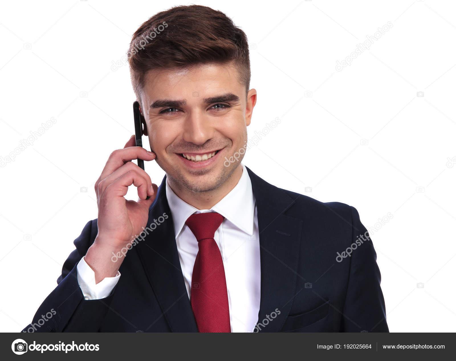87d4120af4bc2 Portrait de bel homme d'affaires qui rit, parler au téléphone, sur fond  blanc. Il porte un costume marine et une cravate rouge — Image de feedough